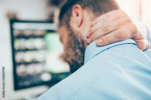 Foto Murales Office worker with neck pain from sitting at desk all day