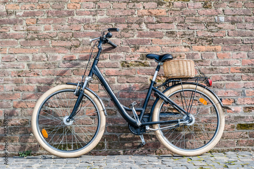 Aluminium Fiets Black retro vintage bicycle with old brick wall.