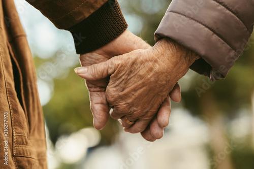 Leinwanddruck Bild Elderly couple holding hands and walking