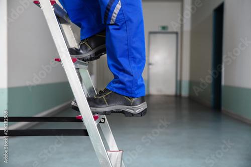 Leinwandbild Motiv Handyman Climbing Ladder