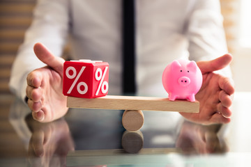 Hand Protecting Balance Between Percentage And Piggybank