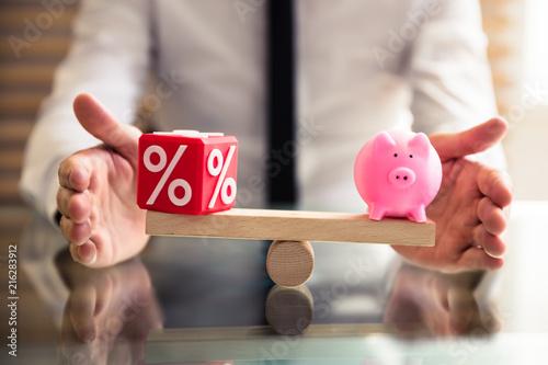 Hand Protecting Balance Between Percentage And Piggybank - 216283912
