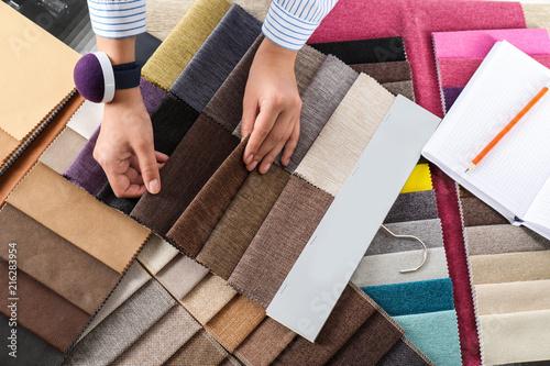 Leinwandbild Motiv Young woman choosing among upholstery fabric samples, closeup. Interior design