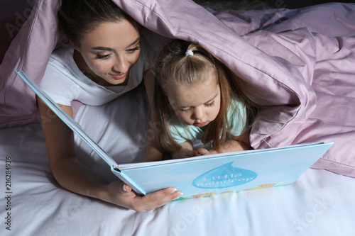 Mother reading bedtime story to her little daughter while lying under blanket