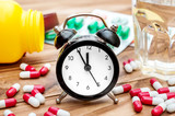 Clock with pills and glass of water on the table. Close up.