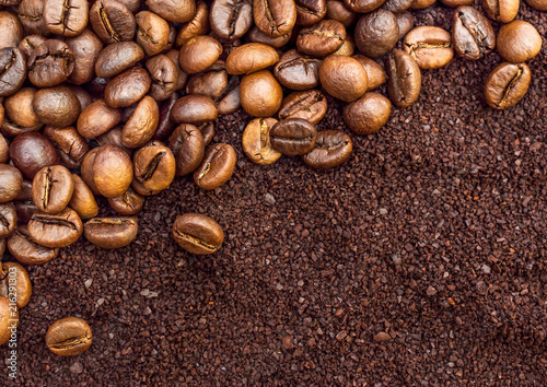 Wall mural Background of ground coffee and coffee beans. Top view.