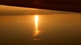 Beautiful golden sun peaking out from under an airplane's wing over the ocean - 216295998