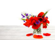 Leinwanddruck Bild - Red poppies, cornflowers, ears of green wheat, chamomile in small vase on white wooden table on white background with space for text.