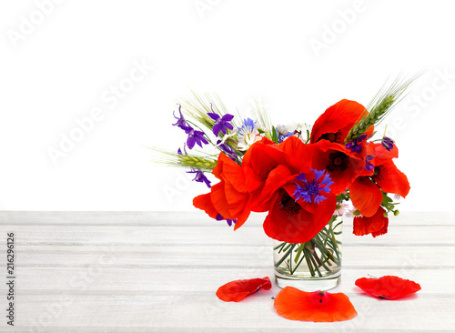 Leinwanddruck Bild Red poppies, cornflowers, ears of green wheat, chamomile in small vase on white wooden table on white background with space for text.