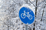 Snowfall in the park, snow covered bicycle sign, snowy treesbackground. cold winter weather concept - 216299708