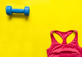 dumbbell and red sports tank top on yellow background, sportswear top view,