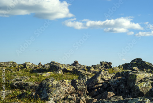 Foto Murales rocky grassy terrain on a mountain pass and a blue sky with clouds above it