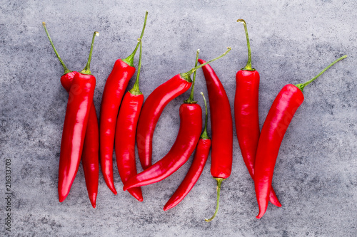 Foto Spatwand Hot chili peppers Chili cayenne pepper on grey background.