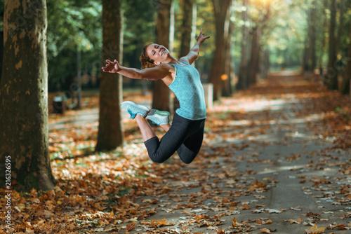 Leinwanddruck Bild Woman Doing Star Jump Outdoors