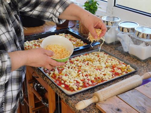Rellenado la pizza con queso rayado.