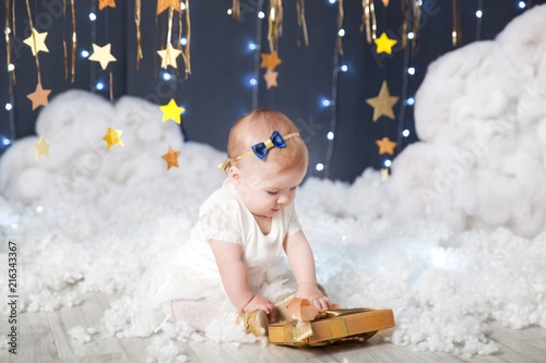 Cute little girl with a present in a studio with a gold stars decor - 216343367