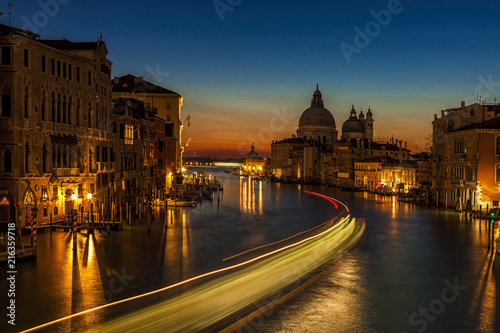 Long exposure of a vaporetto traveling up the Grand Canal towards the Santa Maria della Salute church as seen from the Accademia Bridge
