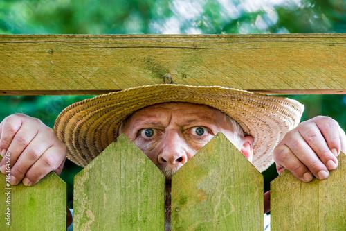 Leinwanddruck Bild ein neugieriger Nachbar sieht über den Gartenzaun