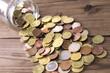 Leinwandbild Motiv jar of coins scattered around the table
