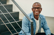 Laughing young African businessman sitting on stairs in an offic