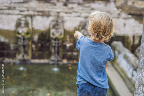 Foto Spatwand Bali Boy tourist in Old Hindu temple of Goa Gajah near Ubud on the island of Bali, Indonesia. Travel in Bali with children concept