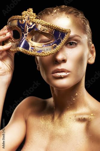 Kobieta z maskarada maska venecian w ręce w pobliżu twarzy. Złota dziewczyna na czarnym tle