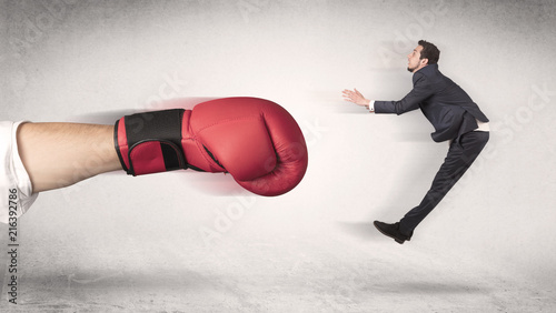 Leinwandbild Motiv Businessman gets fired from his job by a huge hand in boxing gloves