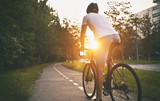 The young guy in casual clothes is cycling on the road in the evening city - 216404187