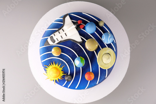 Cake with the image of the cosmos drawn by airbrush. Galaxy, stars, solar system with planets and spaceship. Picture for a menu or a confectionery catalog. Top view. - 216405976