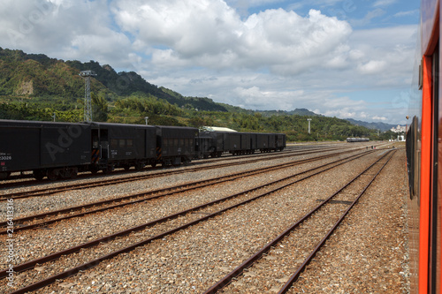Foto Spatwand Spoorlijn Empty old rusted cargo train at the train station in Taiwan. Railroad tracks, rusted metal, goods transportation next to passenger train. Rusted wheels, parallel lines, blue sky and white clouds.