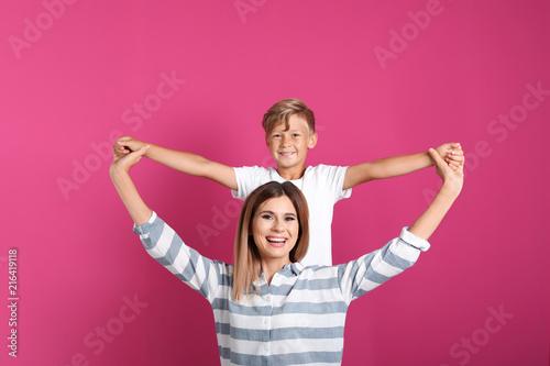 Leinwandbild Motiv Portrait of mother and son on color background