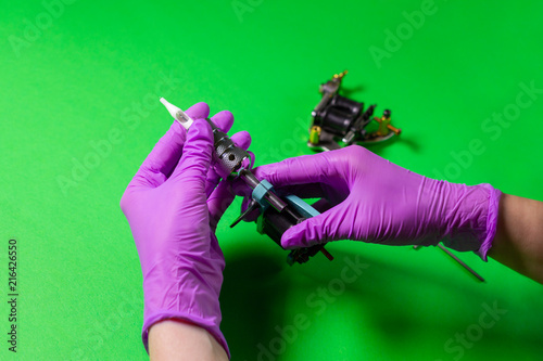 Hands In Pink Rubber Gloves Hold A Blue Tattoo Machine On A Green