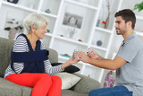 assistant helping smiling senior woman in rest-home