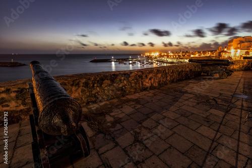 Foto Spatwand Chocoladebruin Paisaje del atardecer sobre el puerto desde los cañones de la muralla de Sines en Portugal