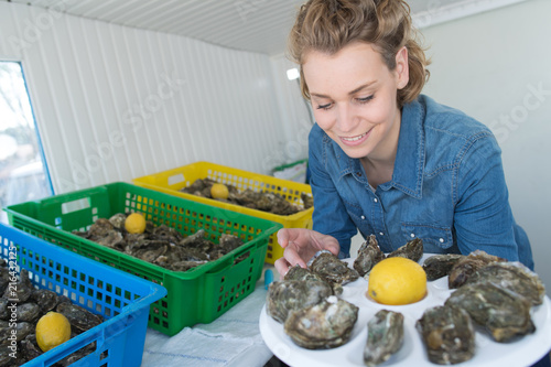 Foto Murales woman preparing a oyster plate to sell