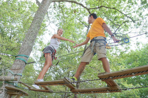 young couple having fun on a rope bridge