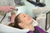 Woman enjoying having her hair washed in salon