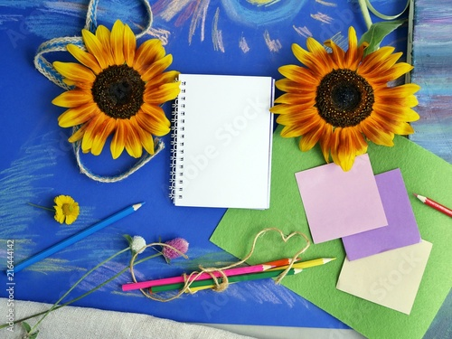 Foto Murales  Bright decorative composition of art materials, notepad and flowers on a chalky blue background, the concept of autumn and school, top view
