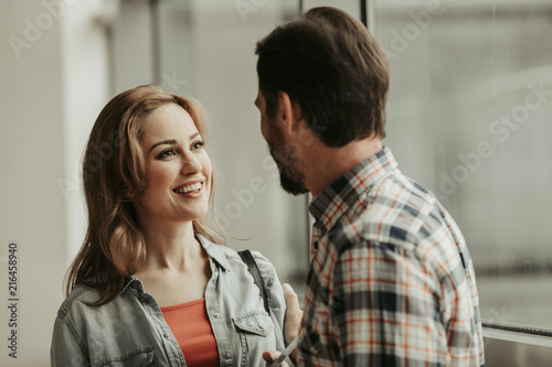 Leinwanddruck Bild Outgoing girl with attractive smile speaking with man indoor. Glad communication concept