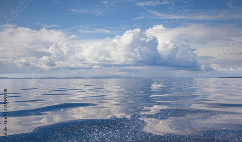 Foto Murales Cumulus white clouds over the water surface of Ladoga Lake. Karelia.