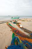 Small fishing boat next to fishing nets drying on Nilaveli beach in Trincomalee Sri Lanka Asia
