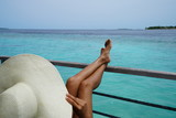 Asian woman sitting, relaxing, overlooking the beautiful turquoise water in The Maldives - 216480955