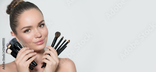 Leinwandbild Motiv Beauty model girl, makeup artist holding set of make up brushes and smiling. Beautiful brunette young woman with perfect skin and nude make-up. Perfect skin