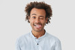 Leinwanddruck Bild - Positive attractive African American male with positive expression, shows tongue, has happy expression, stands against white wall, has crisp hair, have fun together with friends. Funny hipster