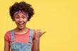 Leinwanddruck Bild - Horizontal shot of joyful curly dark skinned African American female with overjoyed expression, points aside against yellow background, dressed in fashionable dungarees, advertises something amazing
