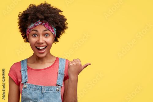Leinwanddruck Bild Horizontal shot of joyful curly dark skinned African American female with overjoyed expression, points aside against yellow background, dressed in fashionable dungarees, advertises something amazing