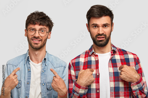 Leinwandbild Motiv Displeased two young men indicate at themself, ask why they should do duties about house, frown face in discontent, wear stylsh shirts, have dark stubbles, isolated over white studio background
