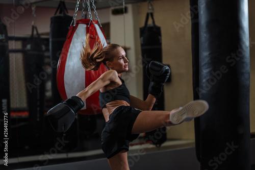 Leinwandbild Motiv bolnd Female fighter in boxing gloves kicks small boxing bag with high leg kick