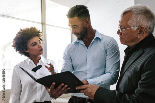 Poster Business team discussing over a business report