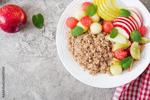 Foto Murales Healthy breakfast. Buckwheat or porridge with fresh melon, watermelon, apple and pear. Tasty food. Top view, copy space, flat lay